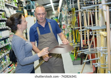 mature happy seller smiling at gardening section of household store