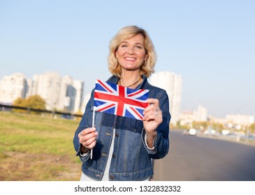 Mature happy woman with flag of Great Britain against blue sky and city.