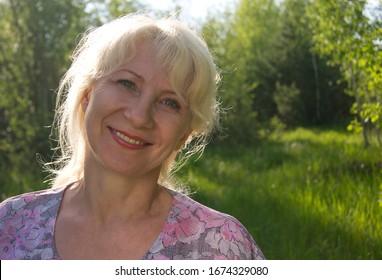 Mature happy woman portrait. Summer photo of beautiful adult female. Blond hair. Joyful face.