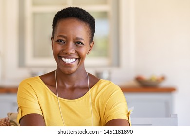 Mature happy woman smiling and looking at camera. Portrait of african american woman in casual clothing and curly short hair relaxing at home.  Portrait of successful black lady with copy space.
