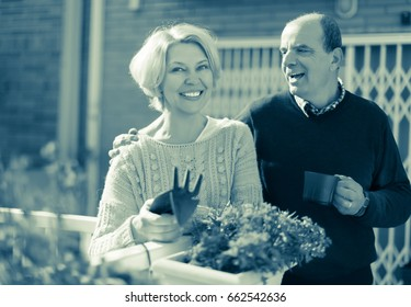 Mature happy woman talking with male neighbor at balcon