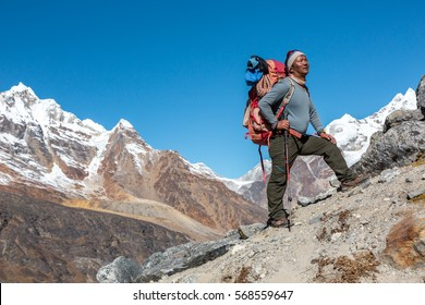 Mature high Altitude Himalaya Nepalese Mountain Guide staying on rocky Slope with Backpack Climbing Gear and looking Up