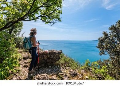 Mature hiker female with backpack looking forward on sea, sky. Travel and active lifestyle concept. Trieste,Italy.