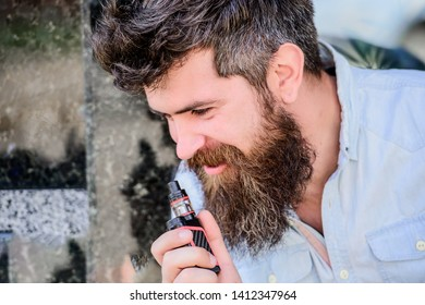 Mature hipster with beard. Bearded brutal male smoking electronic cigarette. man smoking e-cigarette. hipster man hold vaping device. Health safety and addiction. inhaling vapor. Man smoking.