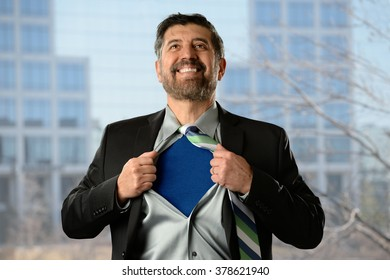 Mature Hispanic businessman opening shirt with office building in background
