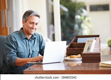 Mature Hispanic Man Using Laptop On Desk At Home