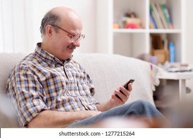 Mature hispanic man wearing eyeglasses checking messages on cell phone