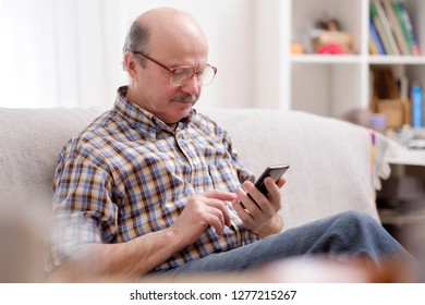 Mature hispanic man wearing eyeglasses checking messages on cell phone