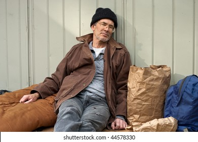 Mature homeless man sleeping in a seated posture, leaning on a metal wall, surrounded by his pack, sleeping bag, etc.