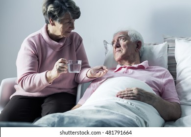 Mature hospice patient and his wife giving him medicines