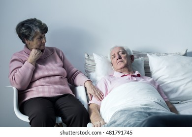 Mature hospice patient lying in a bed and his worried wife