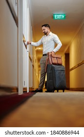 Mature hotel guest opening with luggage opening door of his room in hotel