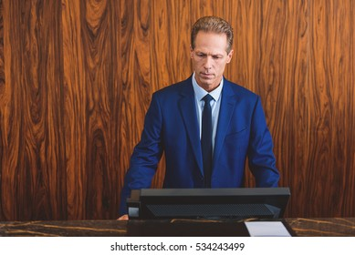 Mature hotelier standing at reception