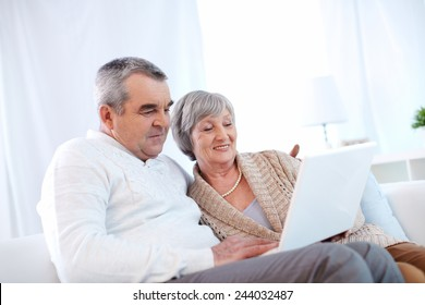 Mature husband and wife using laptop