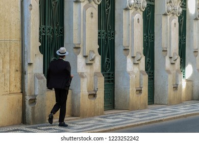 Mature imposing man in vogue black suit and white hat strolling by historical part of city