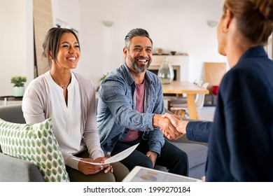 Mature indian man shaking hands with financial advisor at home. Happy smiling couple greeting broker with handshake at home. Multiethnic mid adult man and hispanic woman sealing a contract. - Shutterstock ID 1999270184
