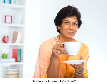 Mature Indian woman drinking coffee / tea at home