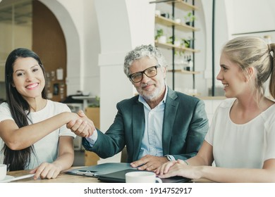Mature investor shaking hands with young entrepreneurs. Man and women meeting over cup of coffee at co-working. Medium shot. Partnership and investment concept
