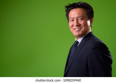 Mature Japanese businessman against green background
