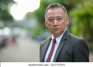 Mature Japanese businessman thinking in the streets outdoors