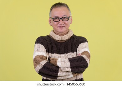 Mature Japanese man with arms crossed ready for winter