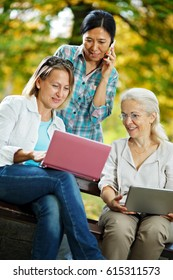 Mature ladies sitting in the park using their laptops