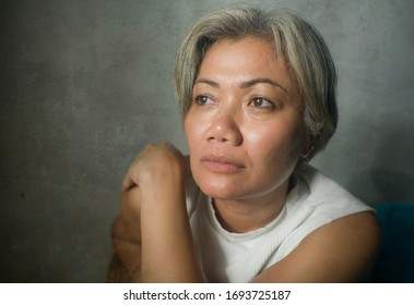 mature lady crisis - indoors lifestyle portrait of middle aged woman with grey hair sad and depressed feeling frustrated and lonely thinking about aging lonely suffering depression