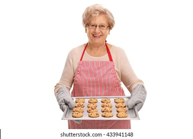 Mature lady holding a tray with homemade chocolate chip cookies isolated on white background