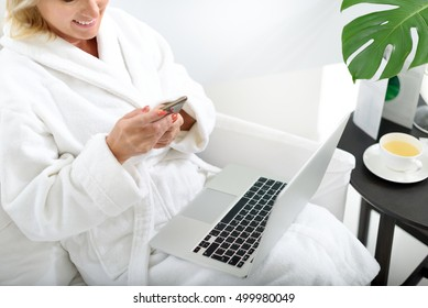 Mature lady with modern gadgets at spa