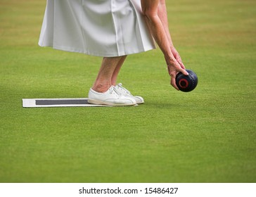 A mature lady player playing lawn bowls.