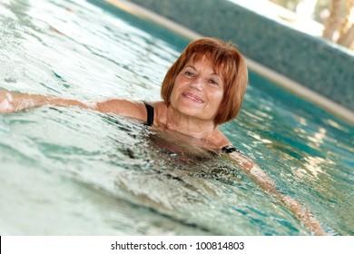 Mature lady swimming at swimming pool.
