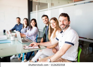 Mature latin man with colleagues making eye contact while sitting in conference room
