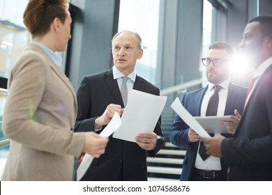 Mature leader of business group explaining information in document to his subordinates at working meeting in lounge