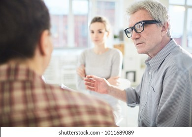 Mature leader of business team looking at one of employees while taking part in discussion of his ideas at start-up meeting