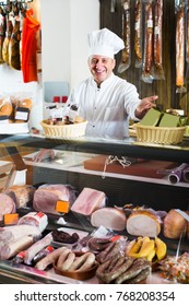 Mature male butcher with wurst, jamon and smoked meat at counter