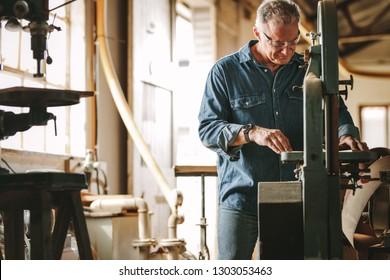 Mature male carpenter working on band saw machine in carpentry workshop. Senior man cutting wood on machine.