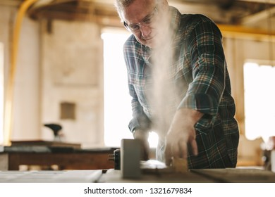 Mature male carpenter working on table saw machine in carpentry workshop. Senior man cutting wood on table saw machine.