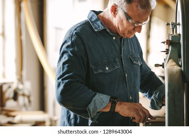 Mature male carpentry worker working in his workshop. Carpenter cutting wood on band saw machine at workshop.