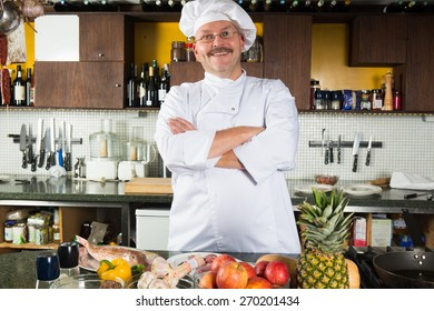 Mature male chef standing in his kitchen ready to start cooking