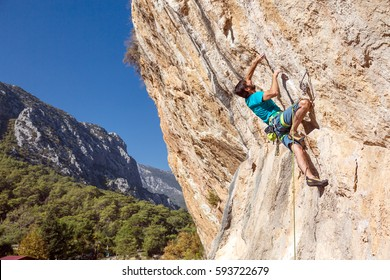Mature male Climber struggling on overhanging orange Rock trying to make a difficult Move