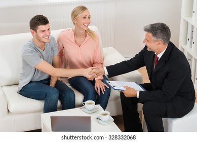 Mature Male Consultant Shaking Hands To Young Happy Man With Wife