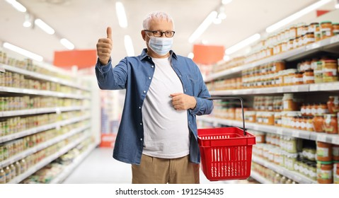 Mature male customer with a face mask and a shopping basket in a supermarket showing a thumb up sign