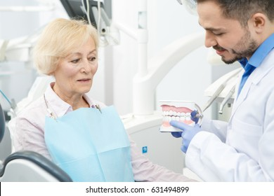 Mature male dentist working with his elderly patient. Senior woman visiting her dentist. Professional dentist showing dental mold to his senior female patient communication advise jaw model dentistry