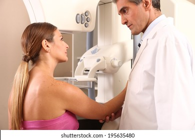 Mature male doctor assisting young patient during mammography.