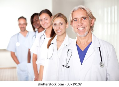 Mature male doctor with his team of colleagues out of focus behind him.