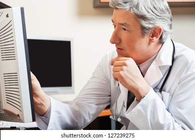 Mature male doctor looking at computer screen in clinic
