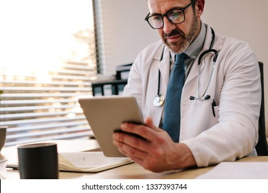 Mature male doctor looking at digital tablet while making notes in his office. Doctor sitting at his desk with tablet computer and writing prescription for his patient.