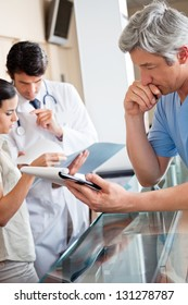 Mature male doctor reading document while colleagues standing at reception
