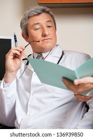 Mature male doctor reading medical report of a patient