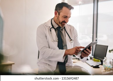 Mature male doctor using tablet computer at his office. General practitioner using digital tablet at his clinic.
